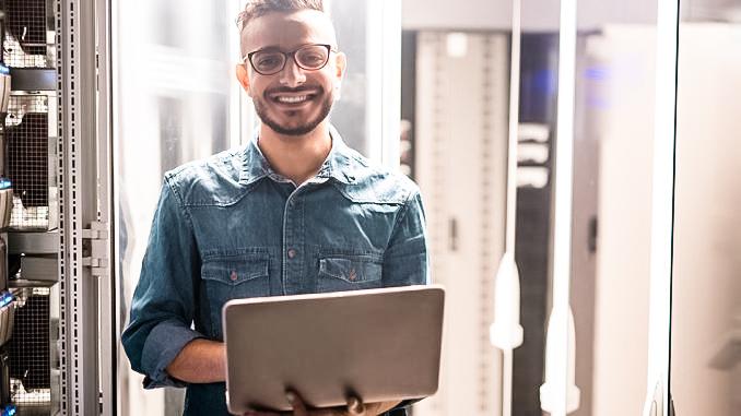 Mann im Datencenter mit Laptop
