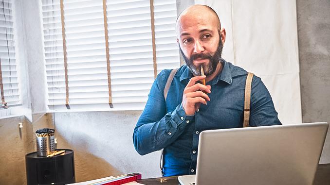 Mann vorm laptop denkt nach