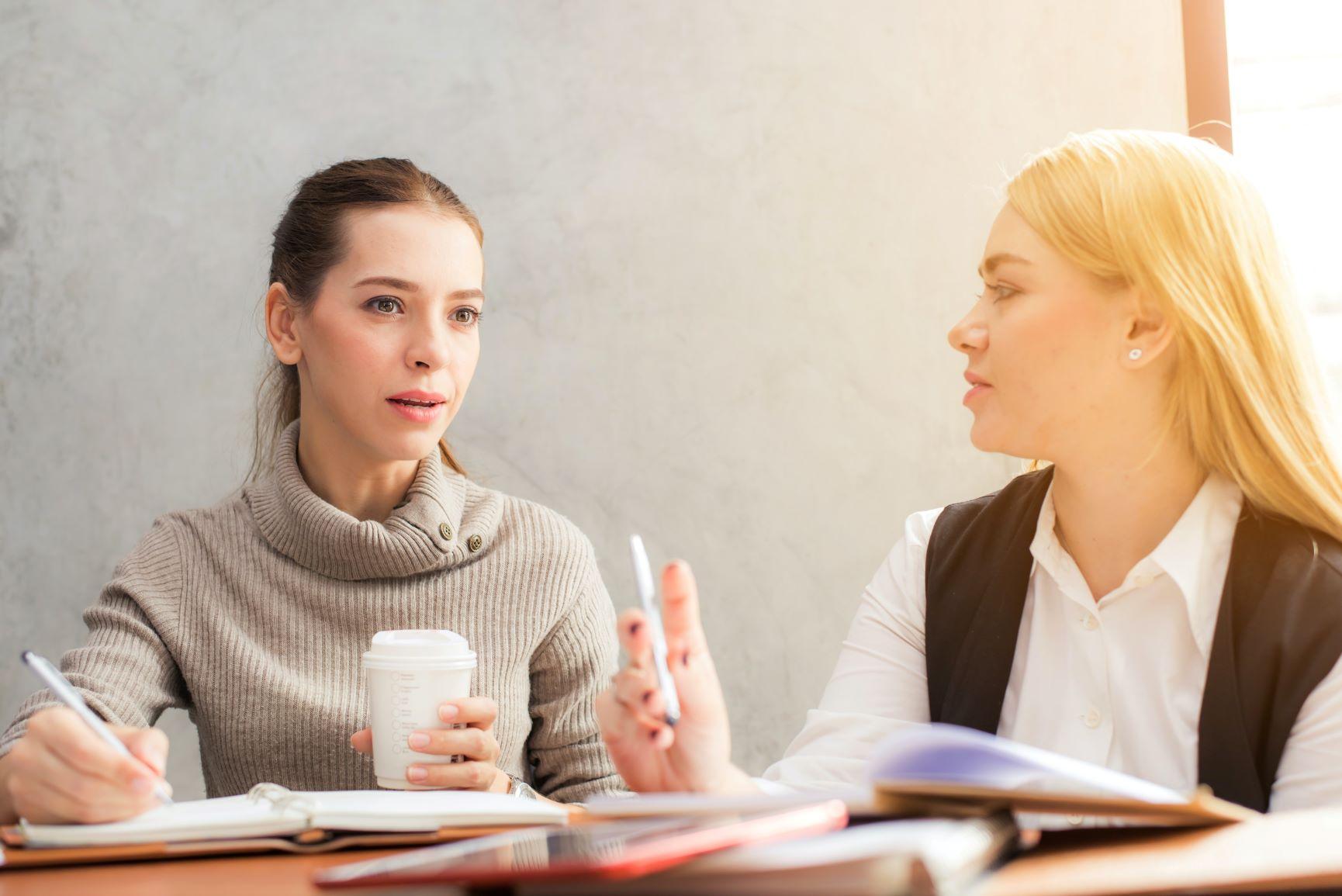 Zwei Frauen unterhalten sich bei Arbeit