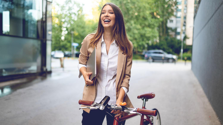 Businessfrau mit Fahrrad unterwegs